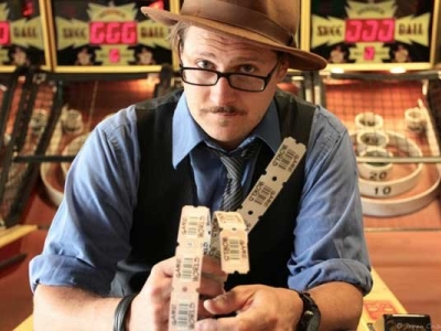 Bryan Russo holding arcade tickets in front of skee-ball lanes