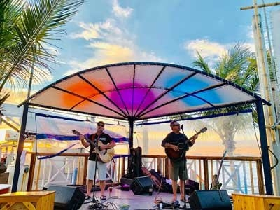 Opposite Directions duo playing guitars on outdoor stage